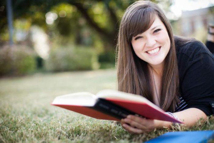 ragazza legge libro in inglese stesa sul prato